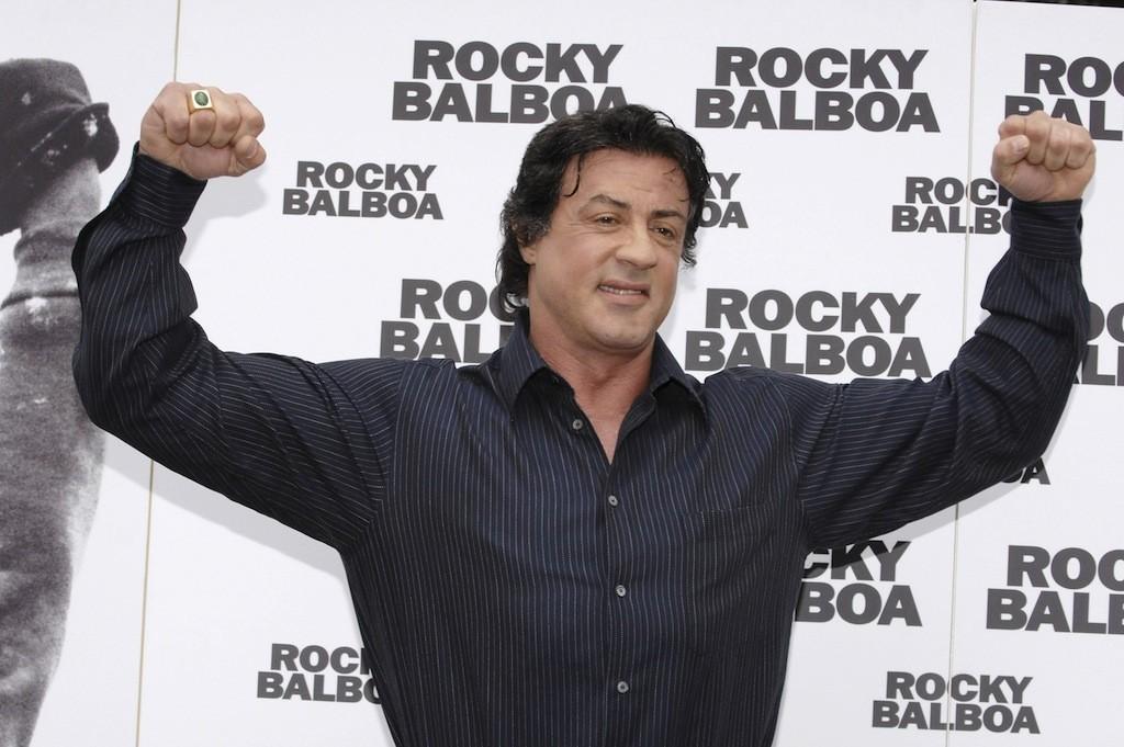 Sylvester Stallone flexes both arms.