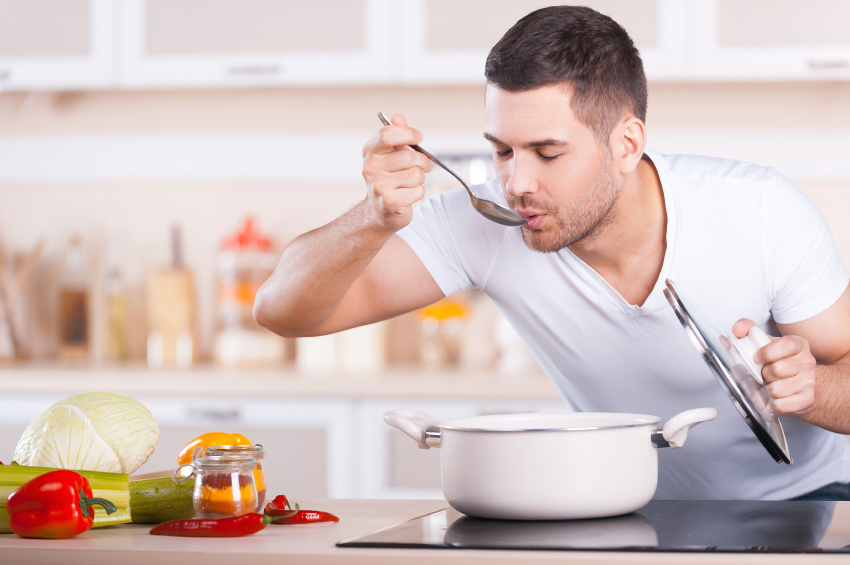 young man cooking and tasting soup from a white pot