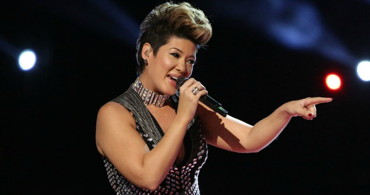 Tessanne Chin is singing and pointing to the left on The Voice.