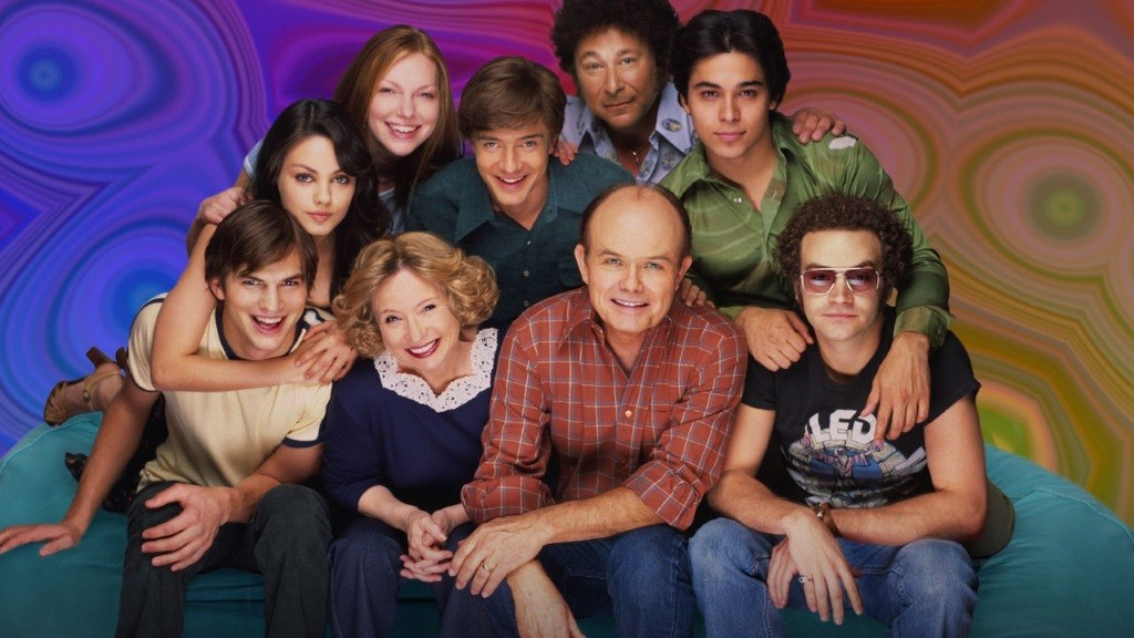 The cast of That '70s Show huddled together with a psychedelic backdrop