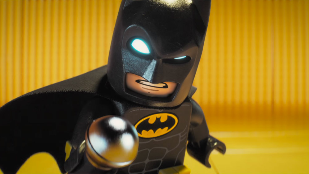Lego Batman holds up a microphone and scowls at the camera