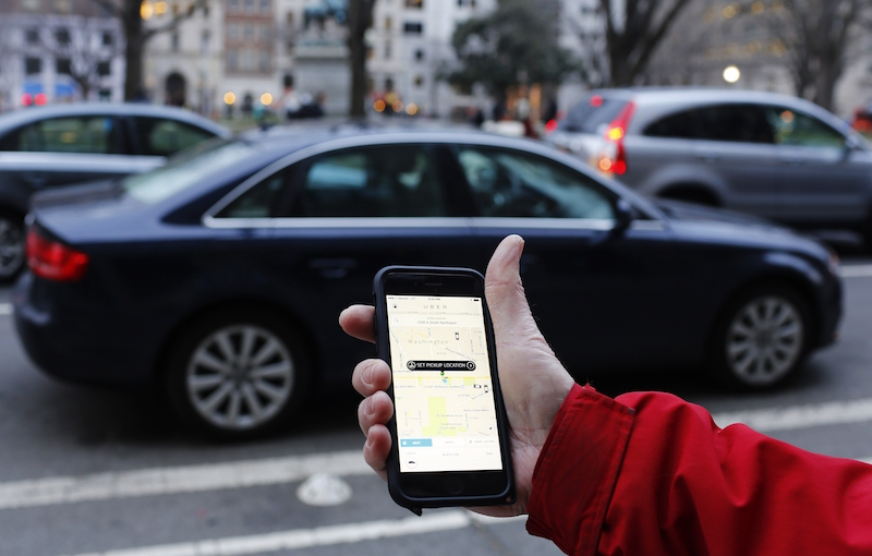 The Uber app shown as cars drive by