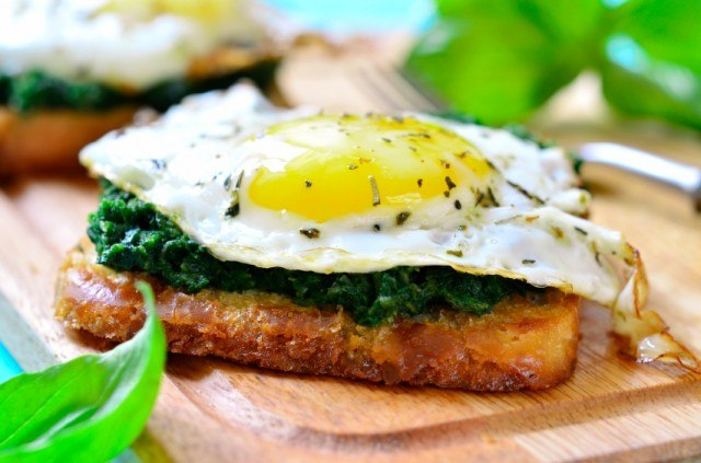 toast toped with wilted greens a a sunny side-up egg