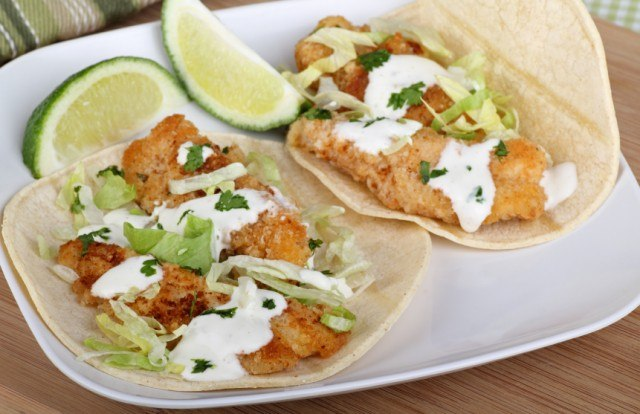 Two fish tacos with two sliced limes on a white plate