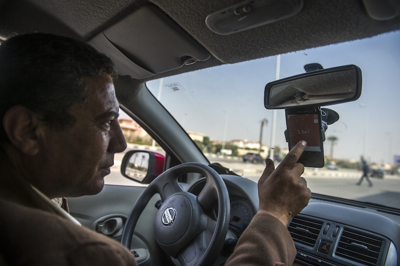 An Uber driver in Cairo checks a map on his smartphone