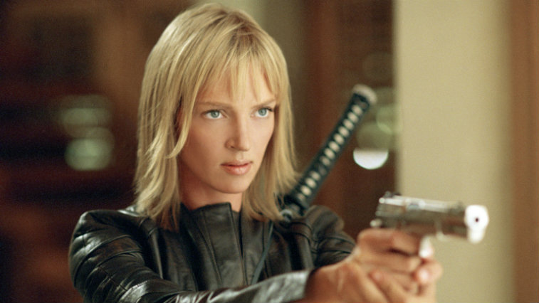 Uma Thurman pointing a gun in Kill Bill while wearing a black leather jacket