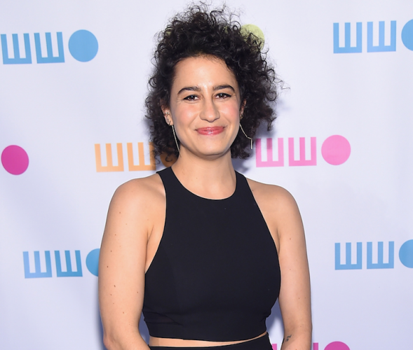 Ilana Glazer smiles and poses for photos on a red carpet.