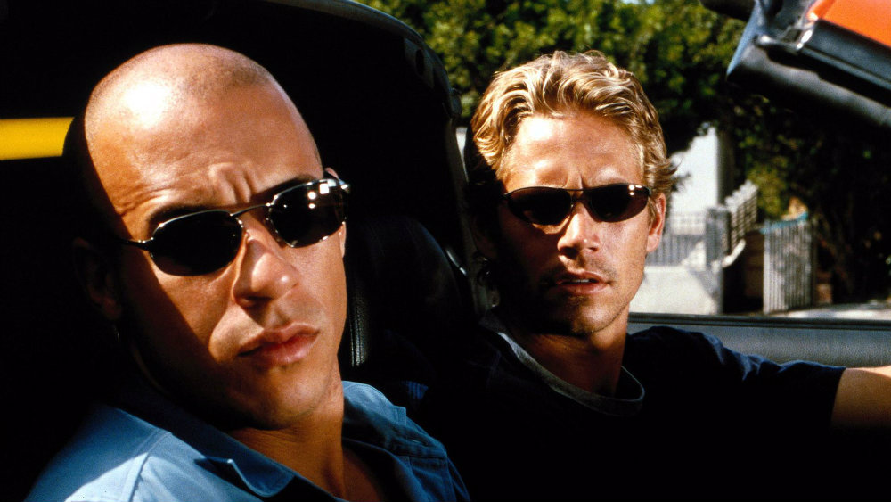 Vin Diesel and Paul Walker in a car wearing sunglasses, both looking to their right