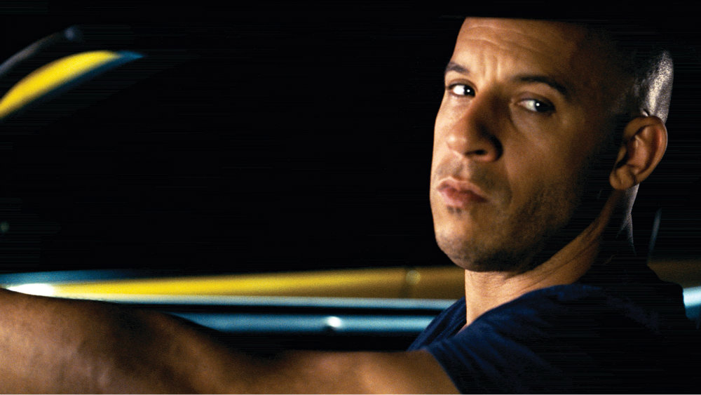 Vin Diesel in Fast Five is looking to the side in the driver's seat of a car.