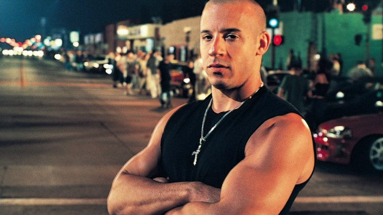 Vin Diesel is standing in front of a line of parked cars.