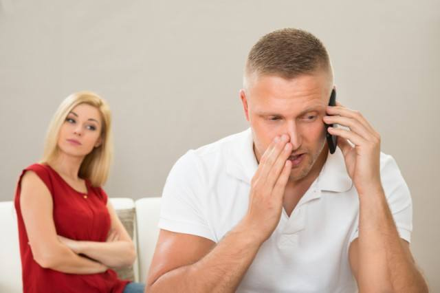 Irritated woman looks on while her husband talks on the phone