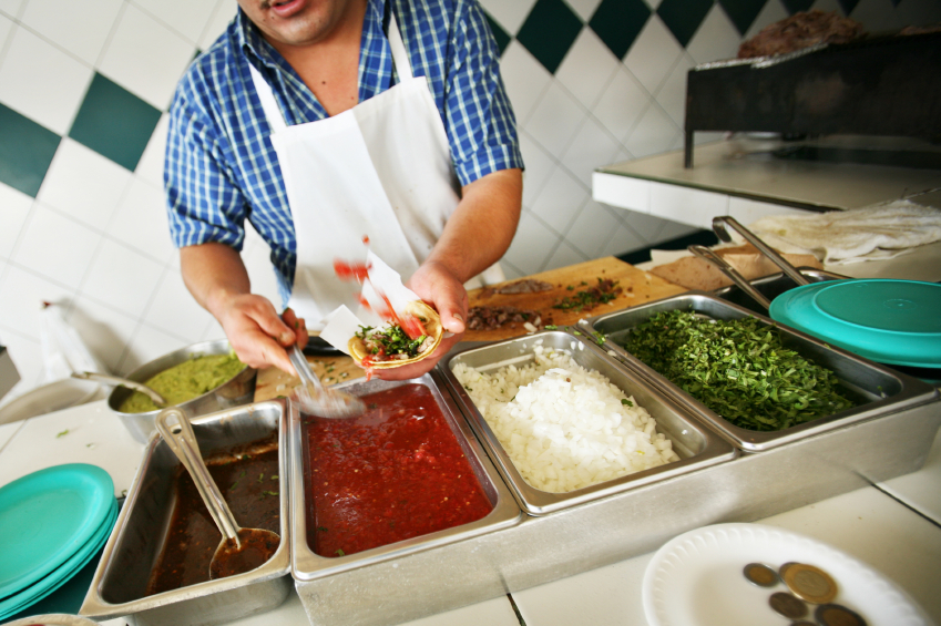 Worker Making Tacos in restaurant kitchen