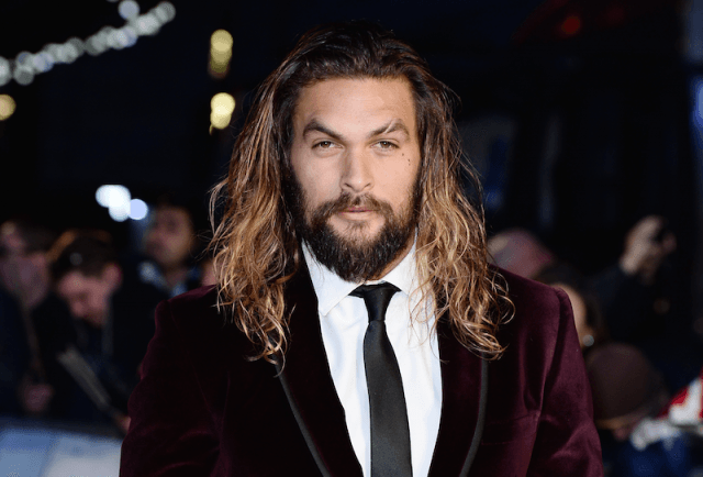 Jason Momoa wearing a suede suit at an event.
