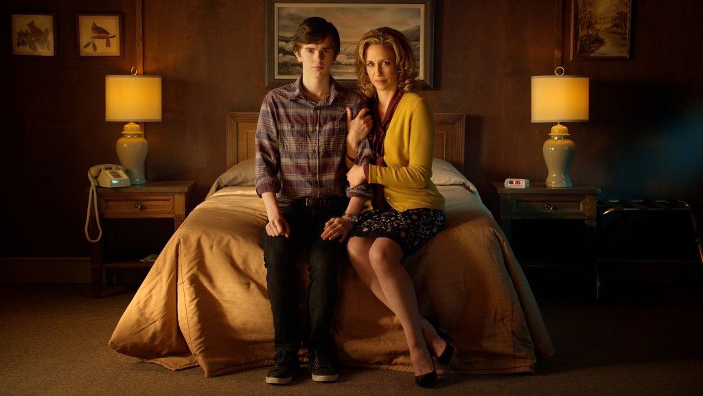 Norma (Vera Farmiga) and Norman (Freddie Highmore) sitting on a bed in A&E's Bates Motel
