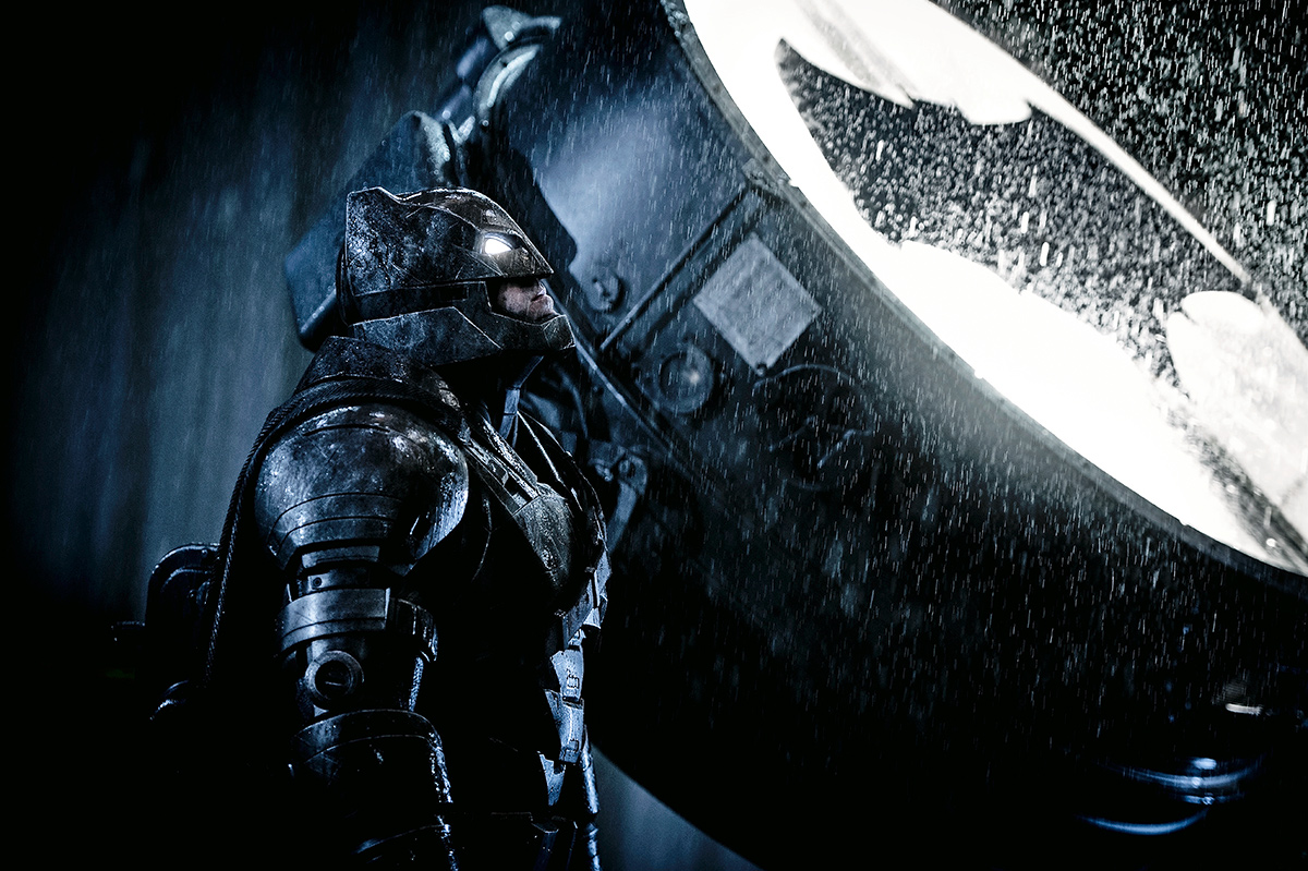 Batman stands next to the Bat Signal in BvS