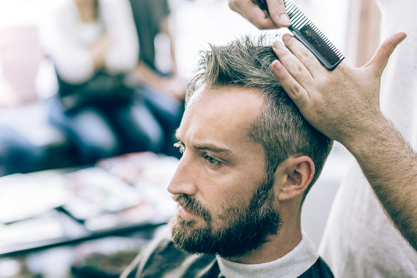 barber cutting hair of young bearded man