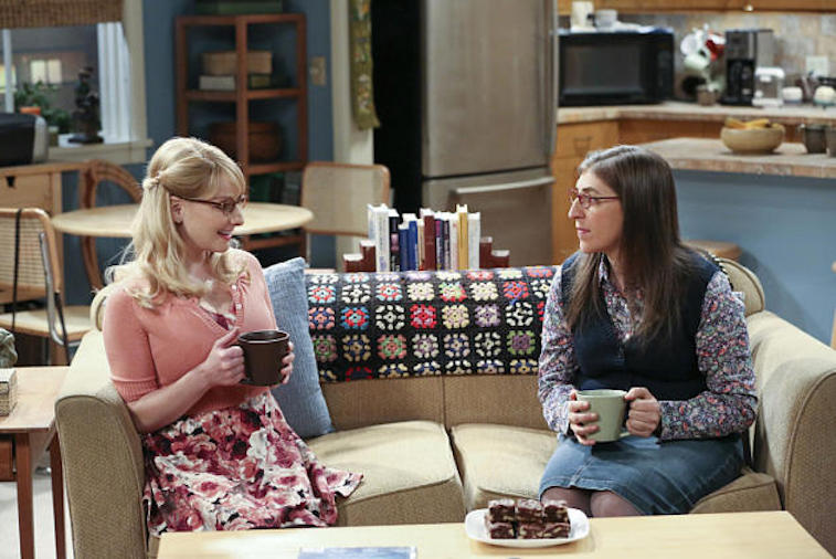 Melissa Rauch and Mayim Bialik talk on a couch in a scene from The Big Bang Theory  