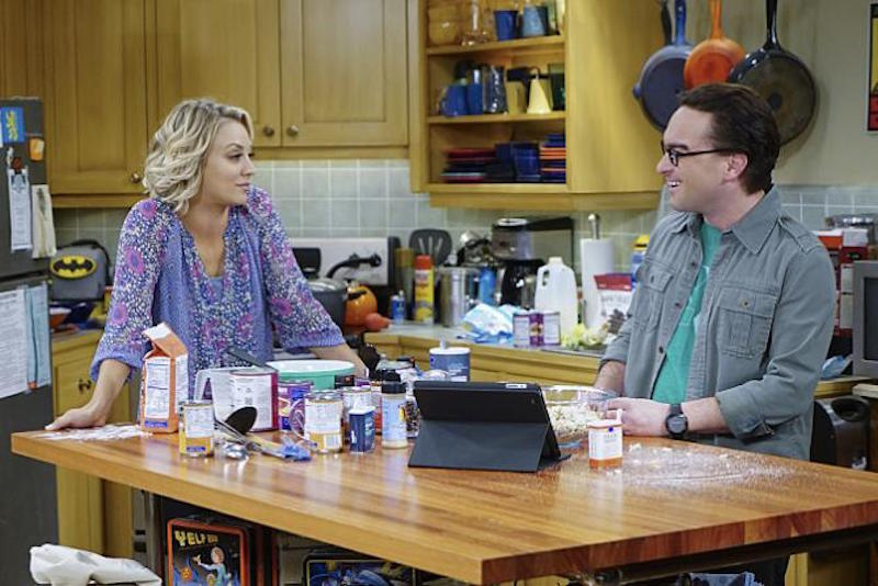 Leonard and Penny stand at a kitchen island in The Big Bang Theory