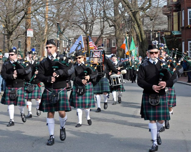 Men wearing kilts adn playing bagpipes for Boston's St. Patrick's Day Parade