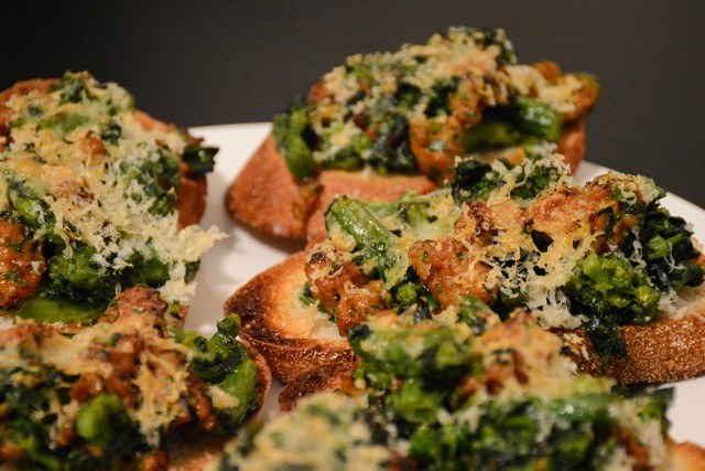 bruschetta topped with broccoli rabe and Italian sausage