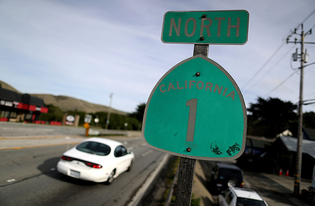 Cars drive by a California route 1 road sign