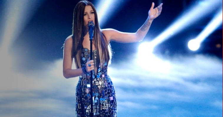Cassadee Pope is singing and lifting a hand into the air.