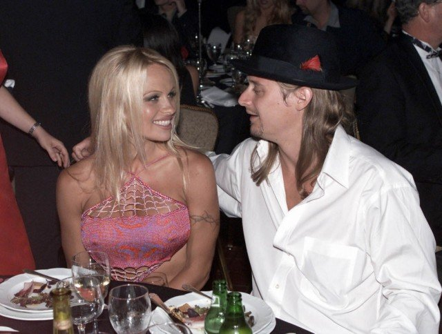 Pamela Anderson and Kid Rock smiling at each other while eating dinner together