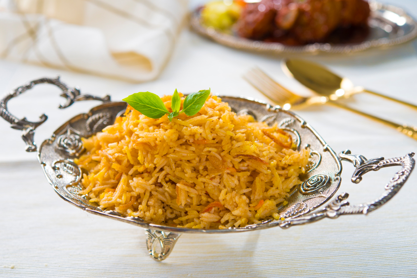 Indian chicken biryani on a silver platter garnished with mint