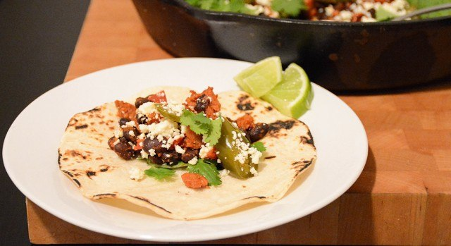 Chorizo-black bean taco with lime wedges on a plate