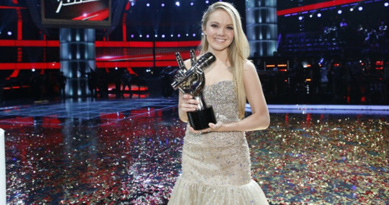 Danielle Bradbery is in a gown and holding a trophy on The Voice.