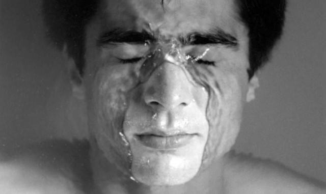 One of Robert Mapplethorpe's photographs, featuring a young man submerging himself in water.