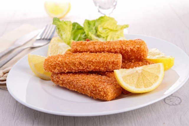 crispy fish steicks with greens and lemon on a white plate