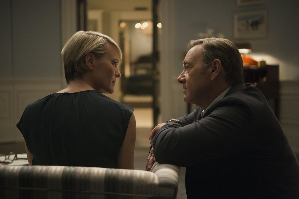 Claire sits on a chair while Frank kneels next to her in House of Cards