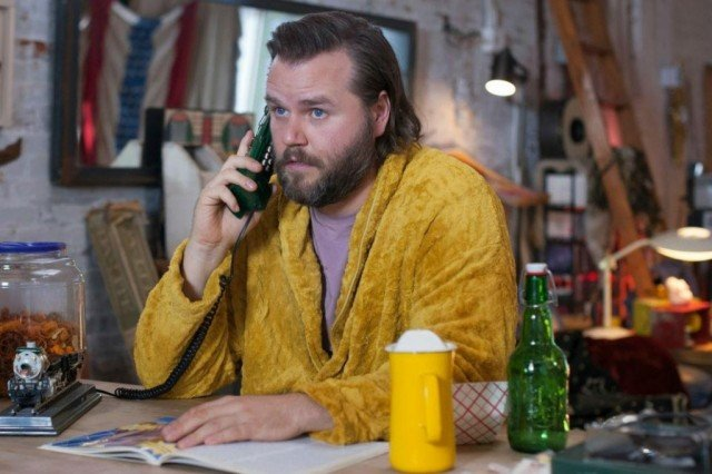 Kevin (Tyler Labine) takes a phone call in a scene from Hulu's supernatural comedy, 'Deadbeat'