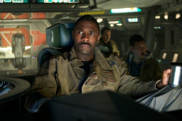 Idris Elba as Janek in a uniform in a commanding chair on a ship holding a cup in Prometheus