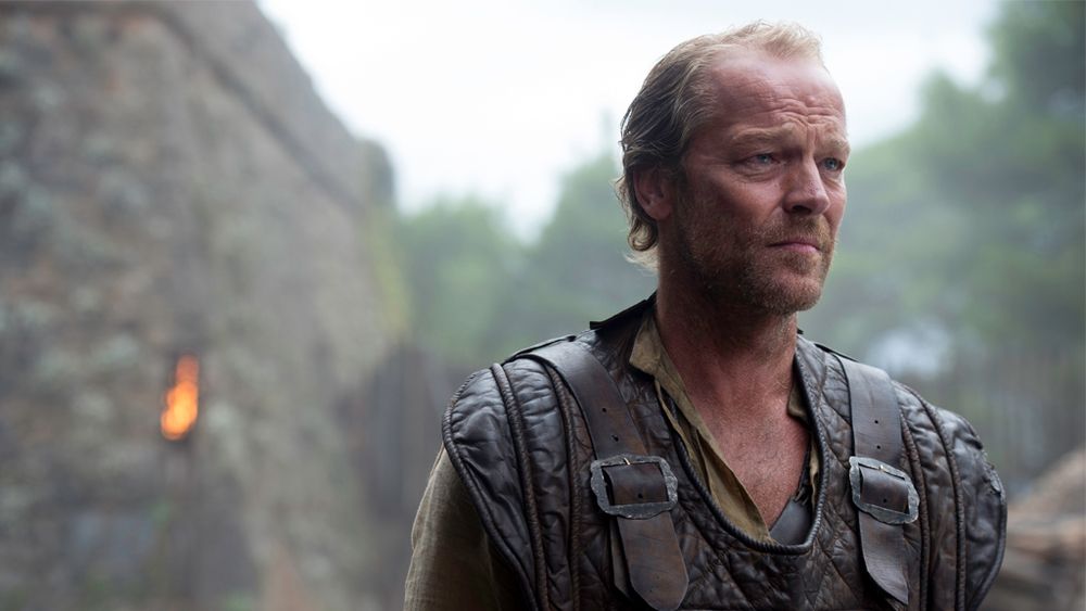 Jorah Mormont is looking ahead and is standing in front of a fortress.