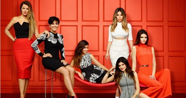 The cast of the Keeping Up With The Kardashians are posing together in a red room.