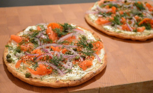 Flatbread with smoked salmon and cream cheese on a cutting board