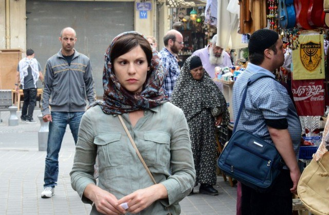 Carrie (Claire Danes) is watched by a suspicious figure as she walks through a crowded market on 'Homeland'