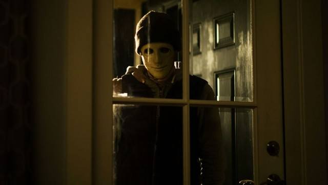 An unwelcome man stands watching in a window in a scene from the SXSW hit 'Hush'