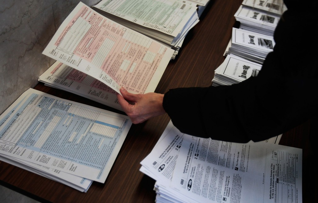 A taxpayer looking over tax forms on table