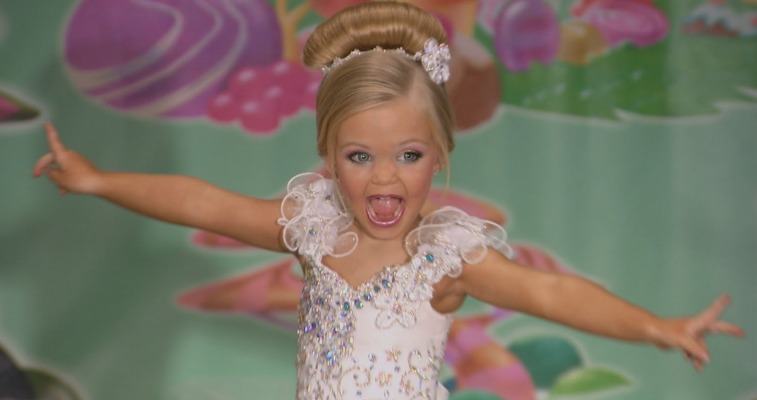 There is a blonde girl posing in a pageant dress.