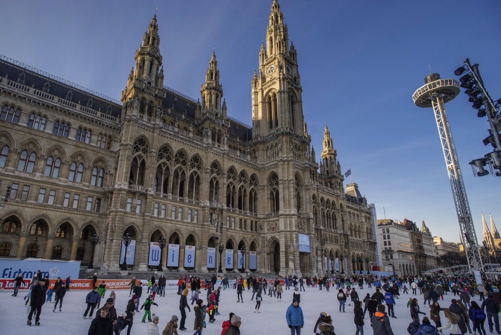 People ice-skate in front of the Vienna City Hall