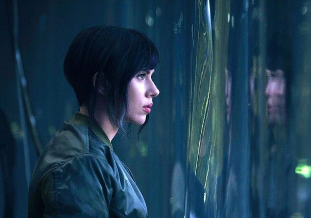 Scarlett Johansson with short hair, sharing to the right of the frame out a distorted window.