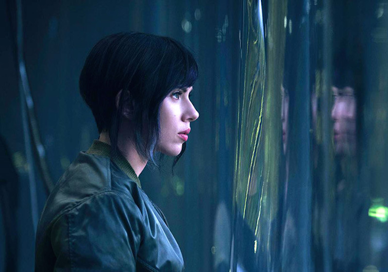 Scarlett Johansson with short hair, sharing to the right of the frame out a distorted window
