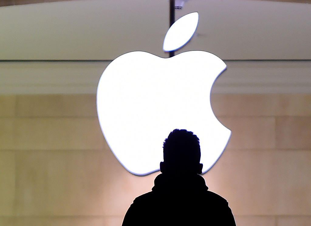 Man standing in front of Apple logo