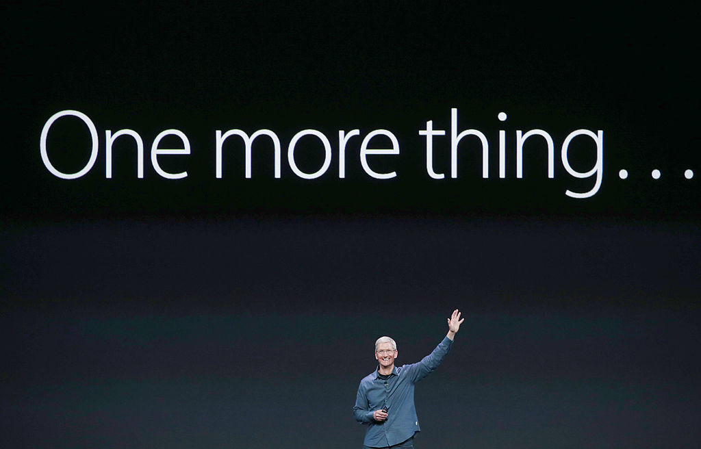 Apple CEO Time Cook pointing to 'One more thing' sign