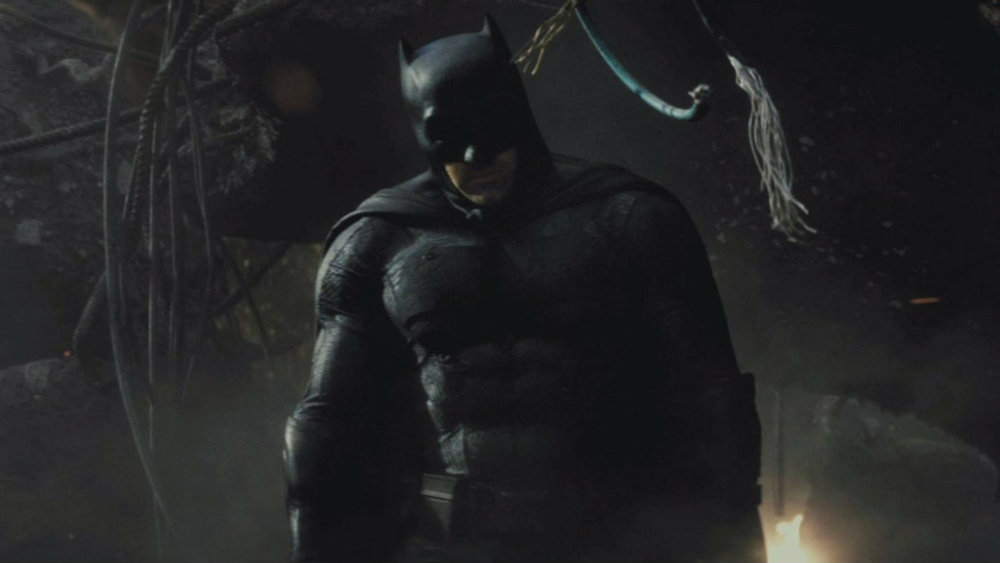 Batman in his full super-suit, walking toward the camera