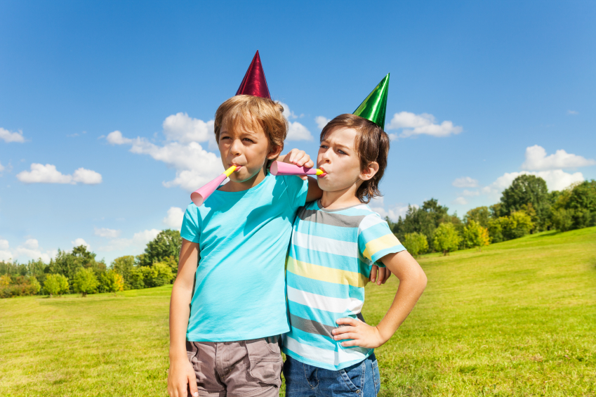 two boys playing with noisemakers at an outdoor party