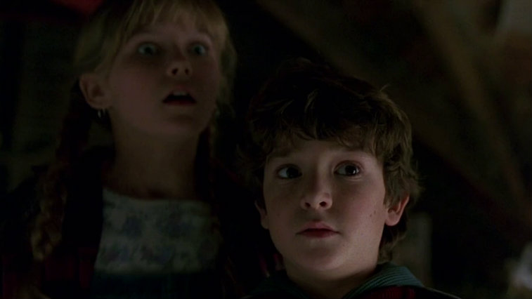 A close-up of a young Kirsten Dunst and Bradley Pierce, both looking shocked to the right of the frame